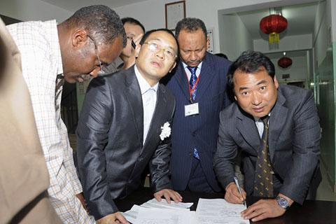 Members of the Chinese embassy in Sudan sign handover papers to receive the body of a worker killed in the kidnapping of specialists who were abducted by South Sudan rebels fighting the government in Khartoum. Despite the partition, fighting continues. by Pan-African News Wire File Photos