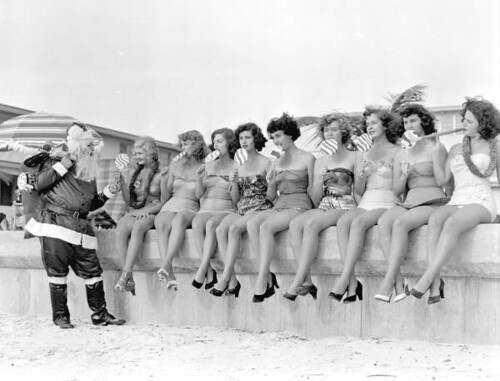 Santa Claus handing out treats to nine young women on the beach: Saint Petersburg, Florida
