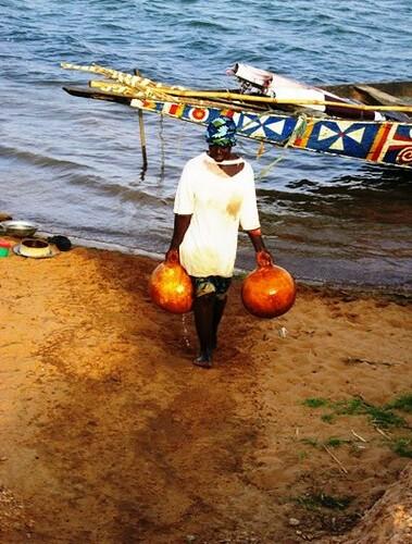 ধান ক্ষেতে পানি দেওয়ার জন্য এক নারী নদী থেকে পানি নিয়ে যাচ্ছে
