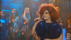 Screen Shot of Bjork on the Colbert Report, she is wearing a blue dress and has big red hair