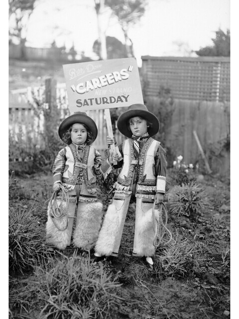 Two children, with poster advertising