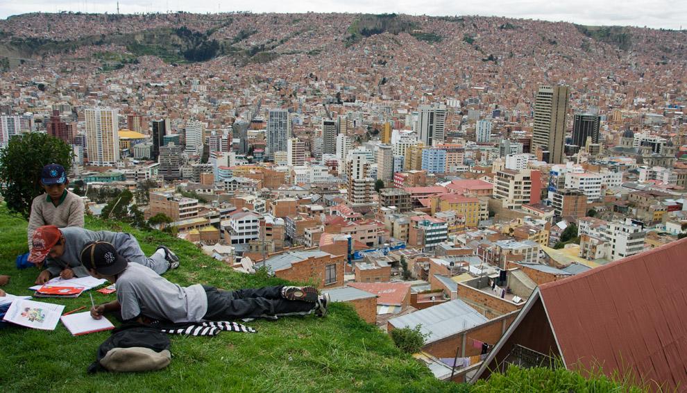 Ni el panorama urbano, ni el acantilado cercano, distraen a los chicos en sus deberes de colegio. La Paz, Bolivia. (Guillermo Morales)