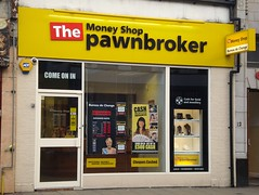 "A small terraced shopfront with a sign reading ""The Money Shop pawnbroker"". The ""The"" is in white letters on a red background and the rest of the sign is in black letters on a yellow background. A projecting sign bears the additional text ""Bureau de Change"". Posters in the windows show smiling light-skinned women. There's a small display of jewellery in the right-hand side of the shop window. A sign above the door reads ""Come on in""."