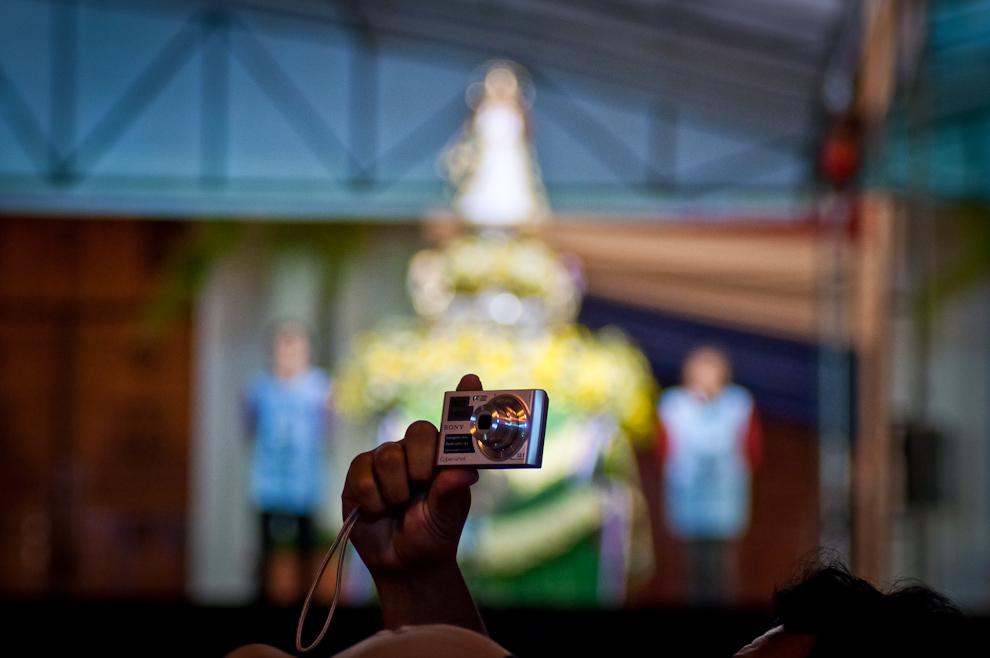 Un hombre levanta su cámara para fotografiar la multitud congregada frente a la imagen de la Virgen de Caacupé mientras se llevaba a cabo el novenario. (Elton Núñez)