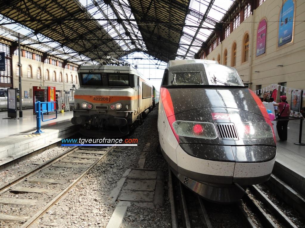 La locomotive électrique BB 22208 SNCF aux côtés de la rame TGV Sud-Est PSE 65 en gare de Marseille Saint-Charles