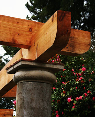 Sturdy cedar rests on cement posts to form the trellis.