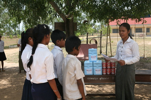 A teacher at Damnak Key School in Cambodia distributes take-home rations to students with good attendance records.  (Photo credit:  International Relief & Development)