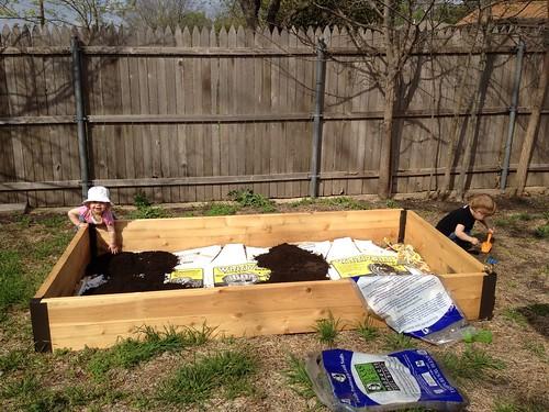Putting dirt in our garden!