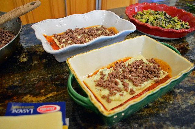 Ground beef mixture being added to partially assembled lasagna.