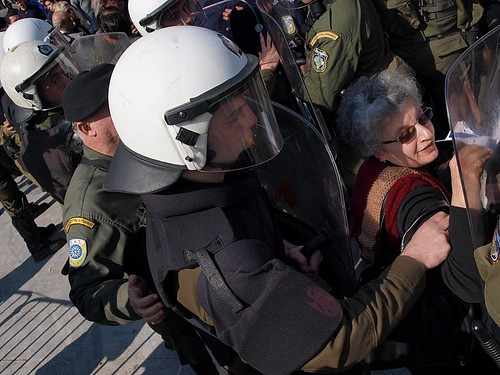 Greek riot police use shield to move protesters away from VIP stands