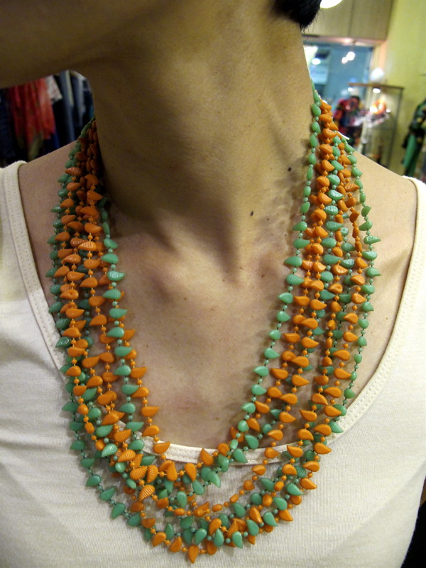 See? See? We love! Orange and green teeny weeny teardrop-shaped beaded multi-strand necklace that you can loop around in a few ways and are too cute for words. We gotta stop using the word cute.