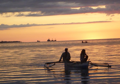 A man and a woman in a boat at dusk (Dili, Timor Leste)