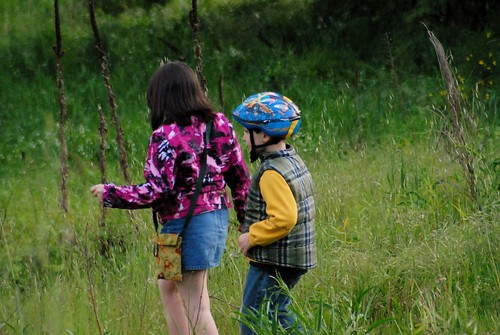 girl and boy with bike helmet in a meadow
