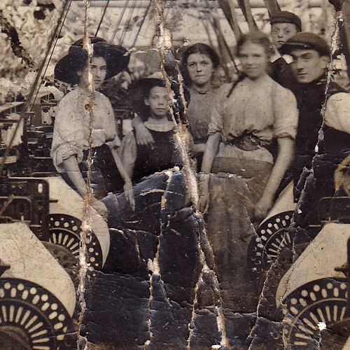 Workers amidst the looms in Oswaldtwistle textile mill, Oswaldtwistle, Lancashire. Decorated for the 1910 coronation. (enlarged detail)