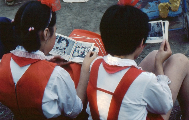 Two girls reading comic books at Sports Day