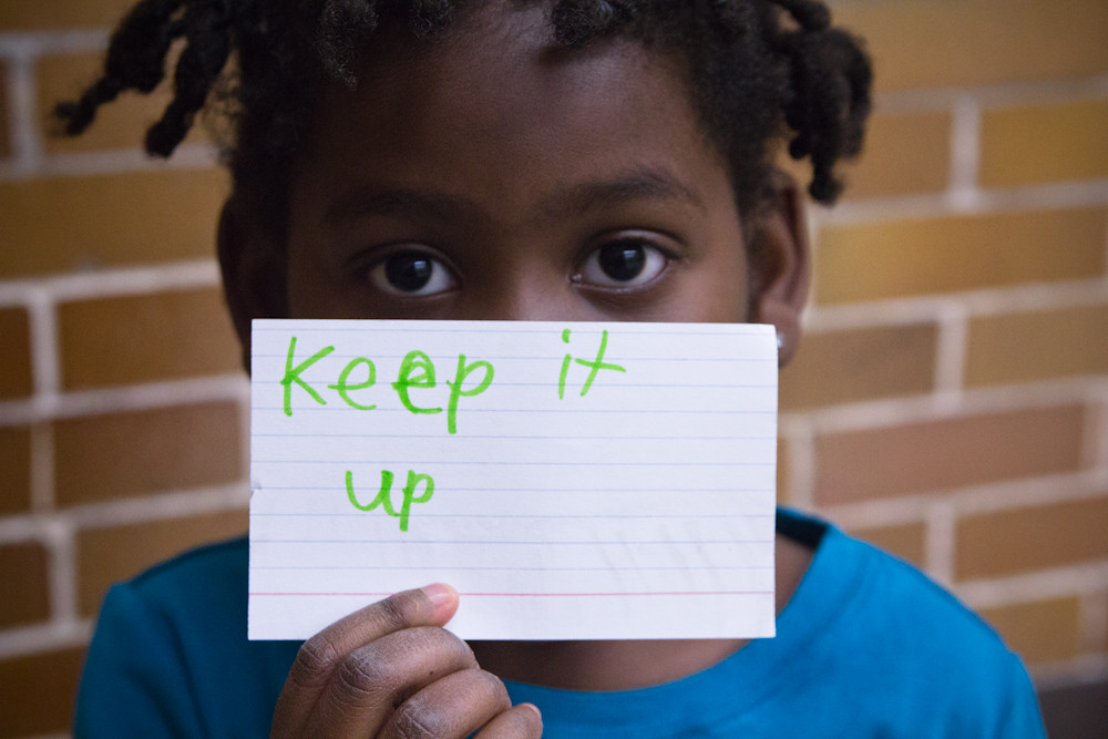 "A young black girl holds up a sign that says ""keep it up"""