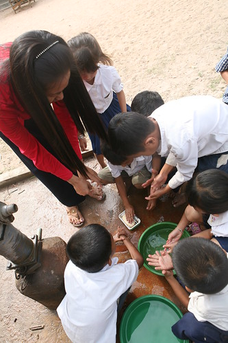 Using the basic hygiene and sanitation skills learned through traditional puppet shows, a teacher and her students at Kirisovanavong school in Cambodia's Kampong Chhnang Province wash their hands before eating. (Photo credit:  International Relief & Development)