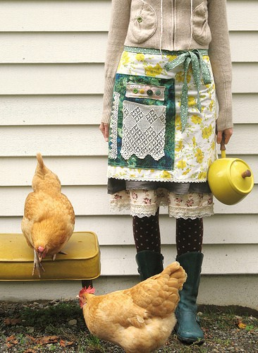 A white woman from the neck down, holding a watering can and wearing an apron. She is surrounded by chickens. From dottieangel.blogspot,com