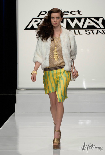 Mila's model in a faux fur coat and striped skirt on the runway