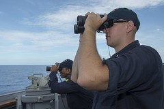 Ensign James Schlup and Chief Electrician's Mate Hector Ortiz monitor surface activity during a routine patrol in the South China Sea by USS Spruance (DDG 111). (U.S. Navy/MC2 Will Gaskill)