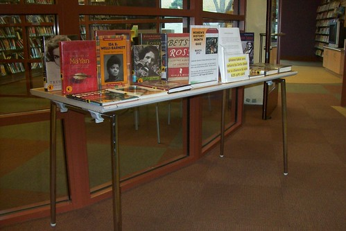 Table with many women's biographies on it along with a sign signifying Women's History Month