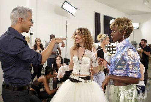"A blonde woman in a room full of models and photographers is talking to Jay Manuel, ""America's Next Top Model"" photo shoot director. She is dressed in Madonna's iconic ""Like A Virgin"" attire."