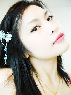Close-up photo of an Asian girl with shoulder-length hair and a butterfly clip