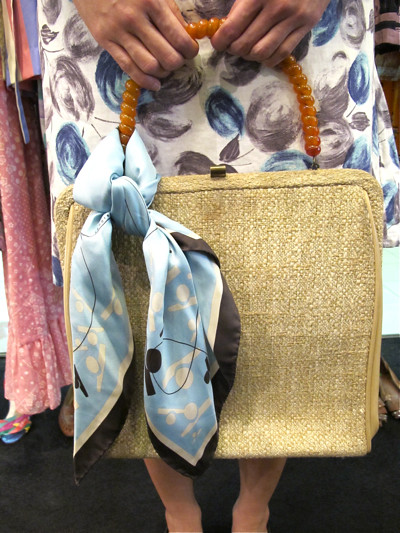 "Scarves make great additions to plain bags, and spruce up the whole look! 1960s bag with lucite handle, tied with a light blue silk scarf in a ""girl guides"" knot."