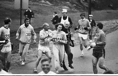 Switzer running the marathon while two men try to grab her number