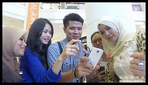 Awal Ashaari and Liyana Jasmay showing or demonstrating the cool features of the Samsung Galaxy S4 to interested buyers.