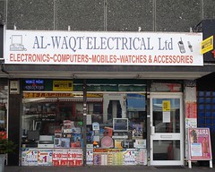 "A small shopfront with boxed and unboxed items of electrical equipment piled up in the front window.  The riser at the bottom is completely covered with posters advertising Lycamobile, GT Mobile, and other mobile phone-related companies.  The sign above reads ""Al-Waqt Electrical Ltd / electronics ~ computers ~ mobiles ~ watches & accessories""."