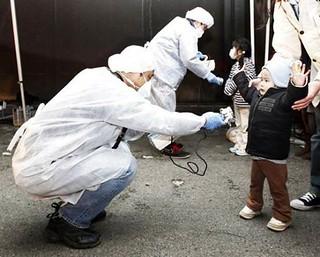 為福島附近的兒童測量放射線數值,圖片來源:路透社。