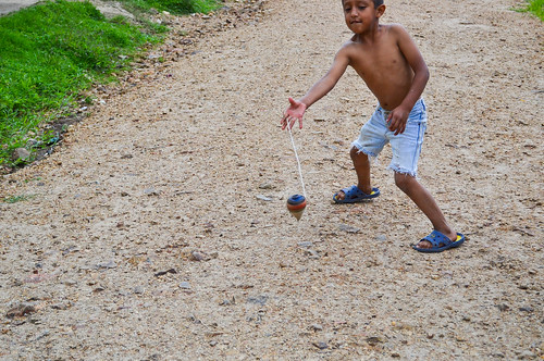 Boy showing tricks in spinning top game