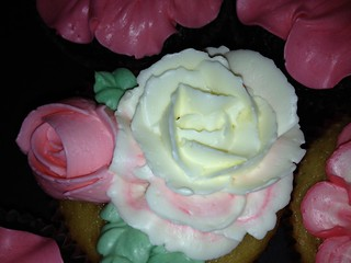 cupcakes with pink and white frosting rose flowers