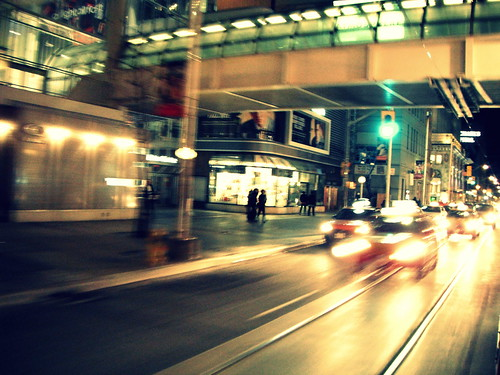 taxis pass Eaton Centre @ night