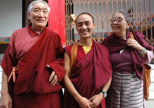 Smiling Tibetan Buddhists attending Sakya Lamdre, Mantho Gyatso, in a traditional men's red chuba, Buddhist monk Manyak Tulku in traditional robes, Chime Sakya Gyatso, wearing a maroon chuba & striped silk Tibetan apron, Tharlam Monastery, Boudha, Nepal by Wonderlane