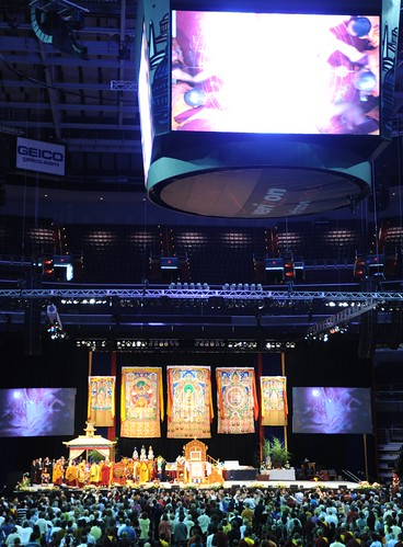 His Holiness the Dalai Lama blessing the Kalachakra Mandala and making offerings, the monitors display a brilliant white light where the mandala is in this photo, Kalachakra for World Peace, Verizon Center, Washington D.C., USA by Wonderlane
