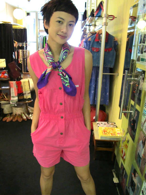 1980s pink cotton romper worn with a vintage Parisian silk scarf around the neck