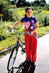 Girl in purple shirt and pink sweatpants standing next to a bicycle.