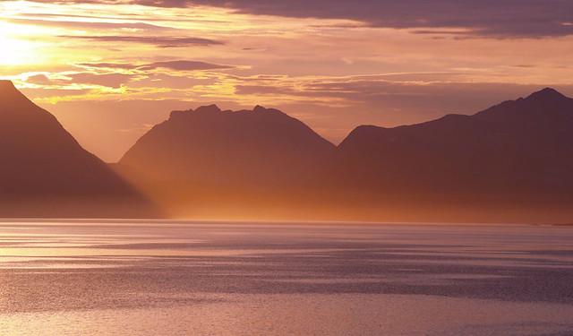 El sol de media noche junto a unas montañas