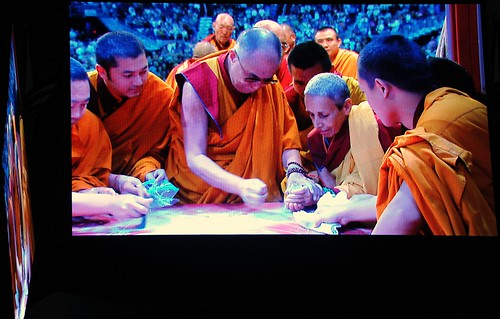 His Holiness the Great 14th Dalai Lama places Kalachakra Mandala colored sand in a small jar for a nun, while lamas wait with plastic bags, monitor, Kalachakra for World Peace, Verizon Center, Washington D.C, USA by Wonderlane
