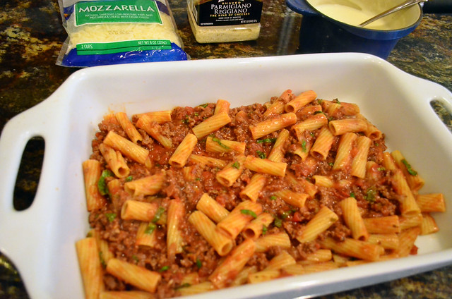 A layer of rigatoni with meat sauce in a white casserole dish.