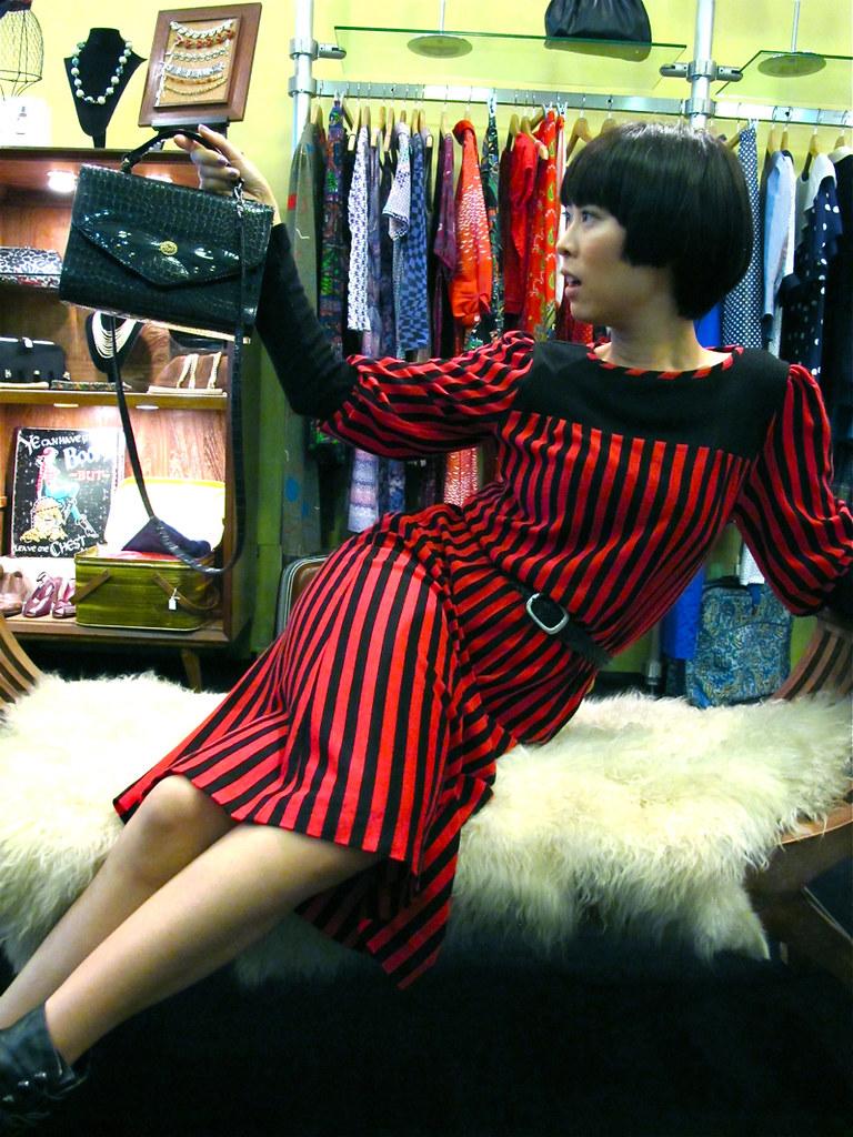 Shes a funny one! If you want to be a high-fashion bag model, hold the bag away from you. X-Wen wears a 1980s red and black striped woolen dress with a black braided leather belt, black high-heeled boots, and holds up a 1980s black sling bag for the world to see.