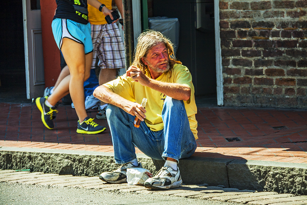 Man-drinking-whiskey-on-curb--New-Orleans