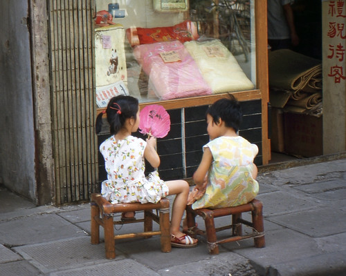 Two little girls in Shanghai sitting outside on a hot day