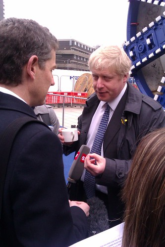 Boris Johnson with cup of tea being interviewed at Crossrail