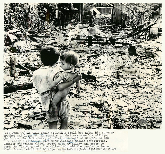 1969 Vietnamese Boy Holds Brother Amid Ruins of Thanh Son