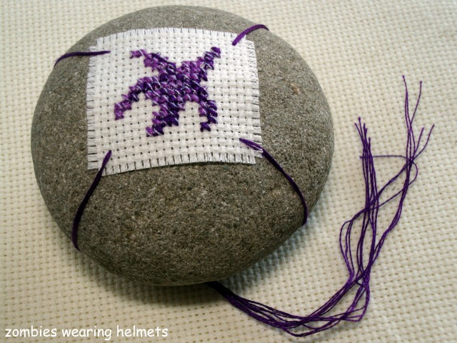 cross stitch starfish mounted on a beach rock