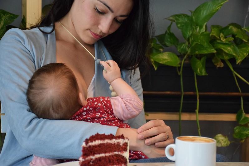 Sujetando el collar de lactancia en lugar del pelo de mamá mientras come.