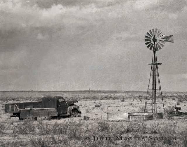a black and white of an abandoned old truck resting next to a prairie windmill on the High Plains of Colorado